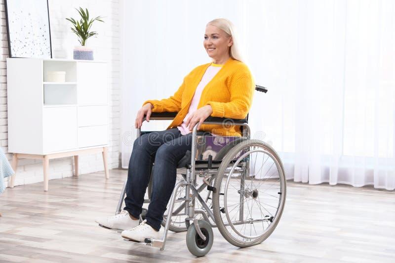 Femme mûre s'asseyant dans le fauteuil roulant photo stock