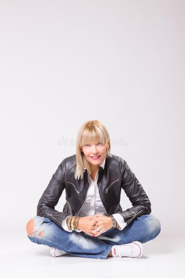 Femme mûre s'asseyant sur le plancher, jambes croisées photo stock