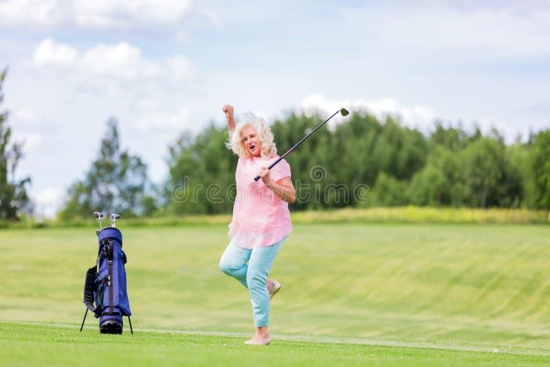 Femme mûre sautant avec le succès sur un terrain de golf photographie stock libre de droits