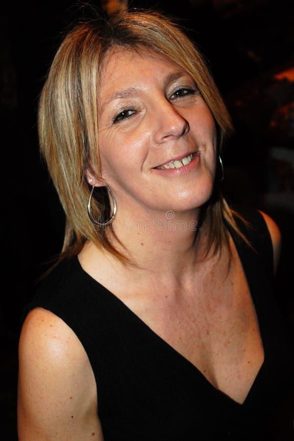 Femme mûre souriant et sereine avec la robe noire photo en buste photographie stock libre de droits