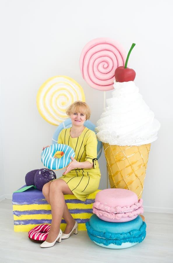 Femme mûre tenant le grand gâteau et posant sur le fond décoré photographie stock libre de droits