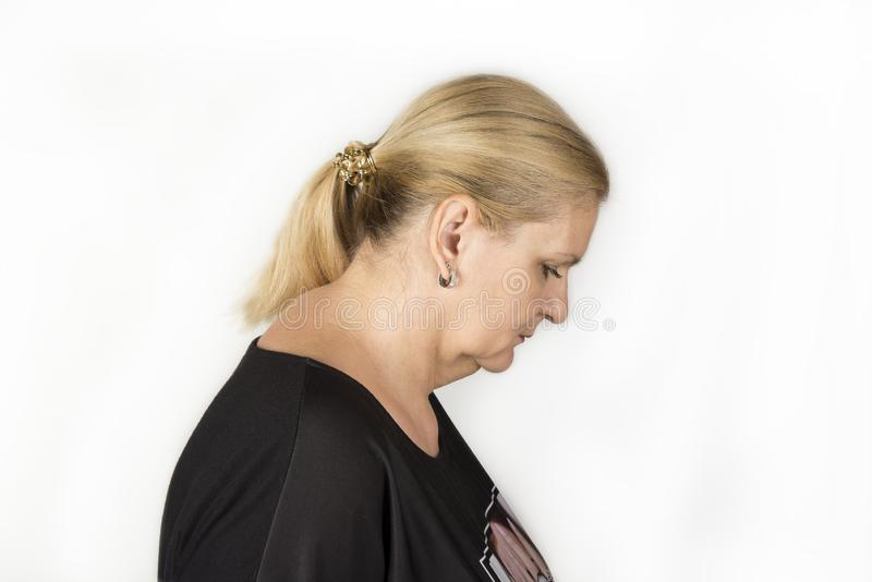 Femme mûre vérifiant le gros soufflet le menton photographie stock