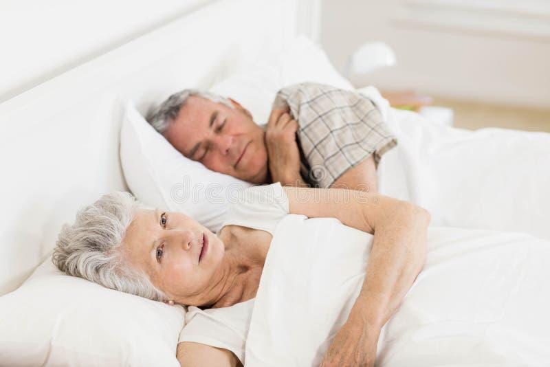 Femme mûre éveillée dans le lit photo libre de droits