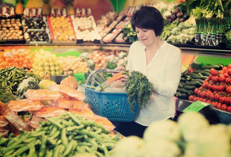 Femme mûre achetant les légumes frais photo stock