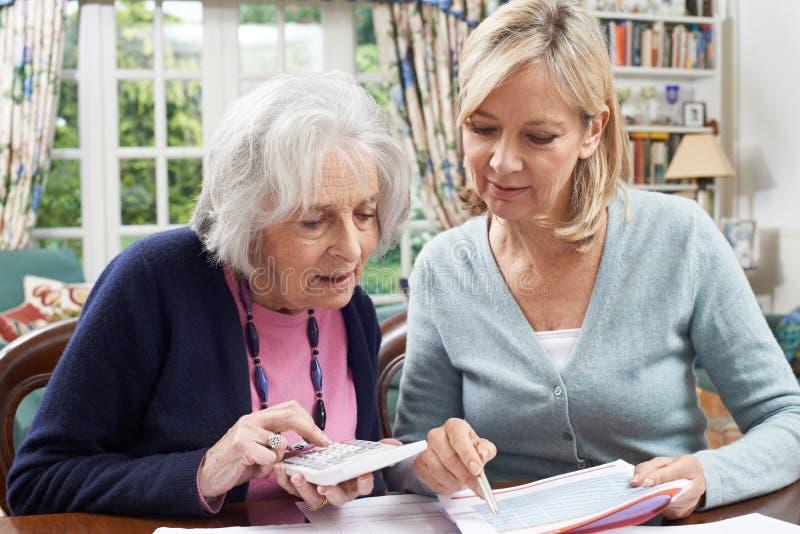 Femme mûre aidant le voisin supérieur avec les finances à la maison photos libres de droits