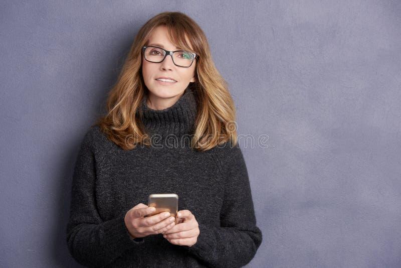 Femme mûre attirante avec le téléphone portable photos stock