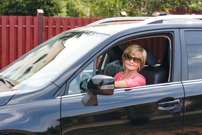 Femme mûre attirante dans une voiture photographie stock libre de droits