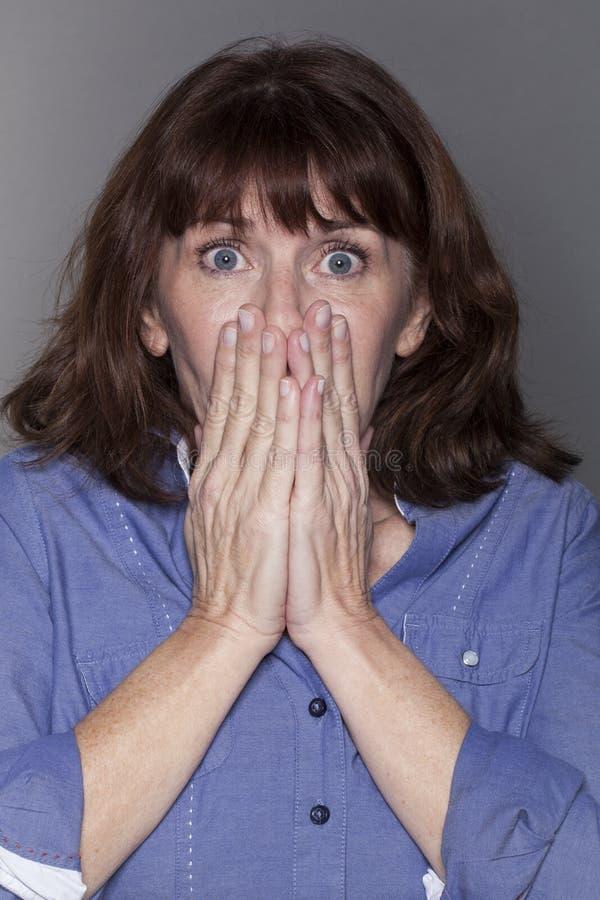 Femme mûre attirante stunned cachant sa bouche photo stock