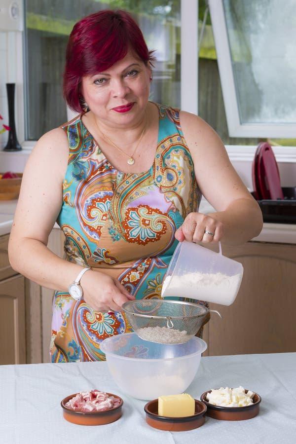 Femme mûre avec de la farine dans la cuisine image libre de droits