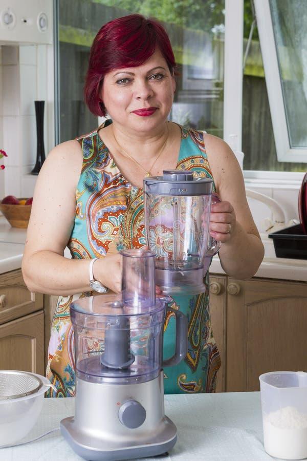 Femme mûre avec des appareils dans la cuisine photographie stock libre de droits