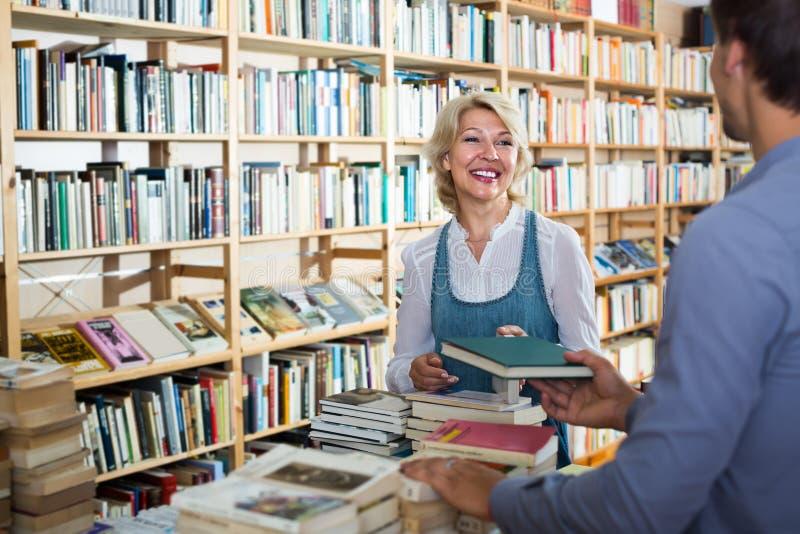 Femme mûre avec l'assistant dans la librairie photos stock