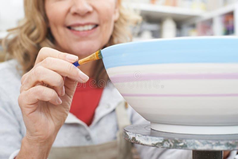 Femme mûre décorant la cuvette dans la classe de poterie photographie stock libre de droits