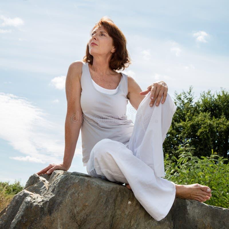 Femme mûre de pensée de yoga détendant dehors photo libre de droits