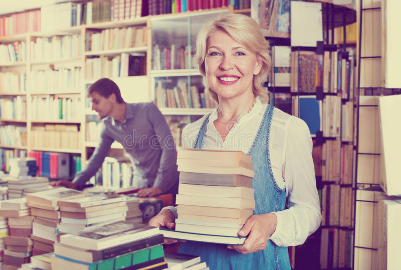 Femme mûre de sourire tenant la pile de livre photos stock