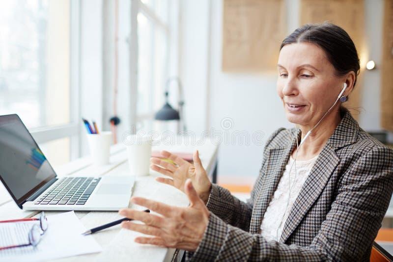 Femme mûre de sourire travaillant en café photo stock