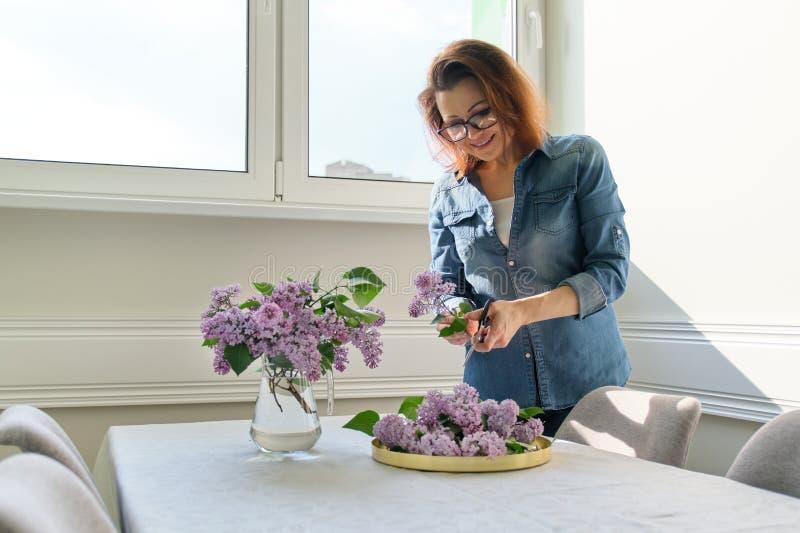Femme m?re faisant le bouquet des branches lilas ? la maison ? la table photos stock