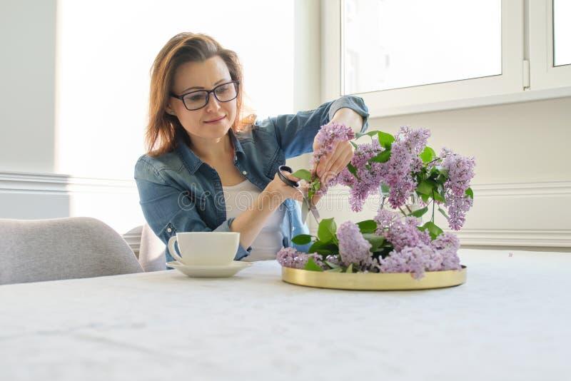 Femme m?re faisant le bouquet des branches lilas ? la maison ? la table images libres de droits