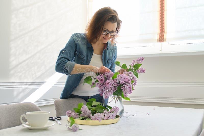 Femme m?re faisant le bouquet des branches lilas ? la maison ? la table photo libre de droits