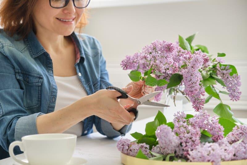 Femme m?re faisant le bouquet des branches lilas ? la maison ? la table photographie stock