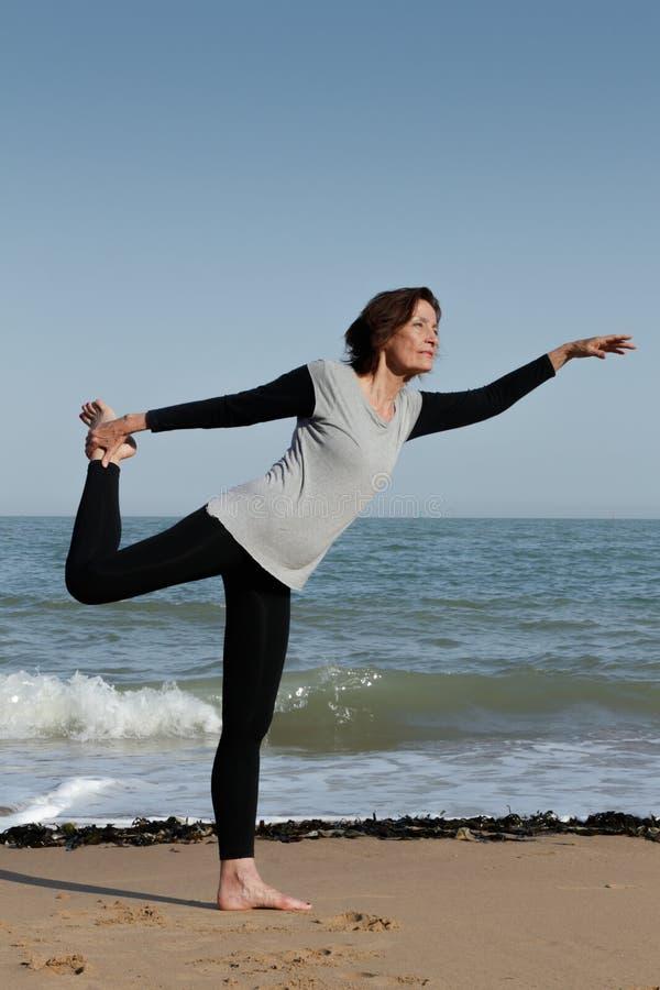 Femme mûre faisant le seigneur de yoga de la danse sur la plage photo libre de droits
