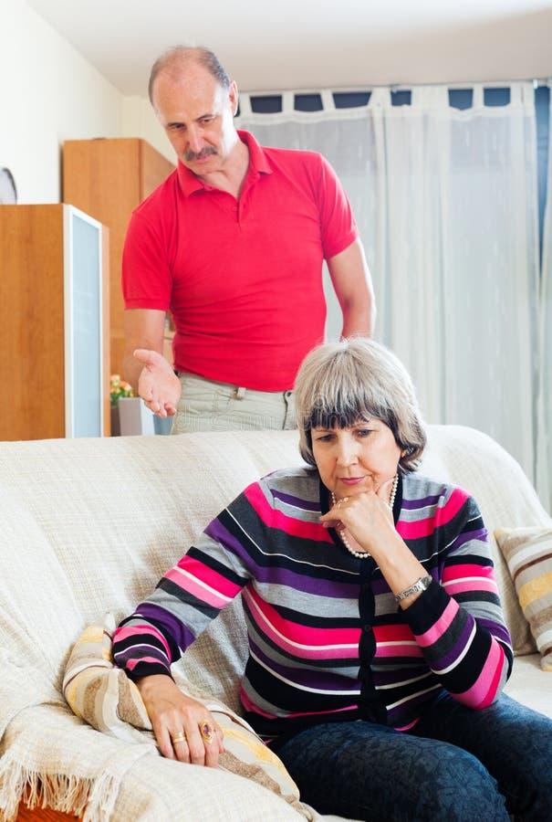 Femme mûre fatiguée écoutant le mari fâché images stock