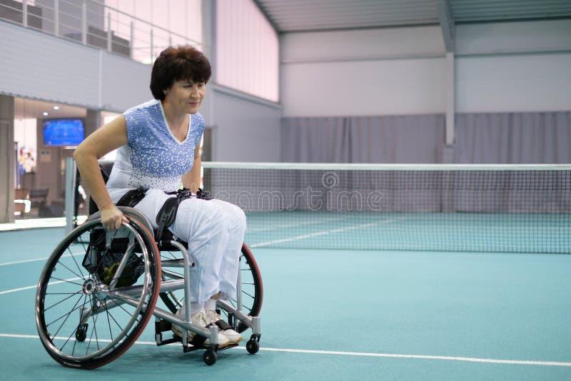 Femme mûre handicapée sur le fauteuil roulant sur le court de tennis photos libres de droits