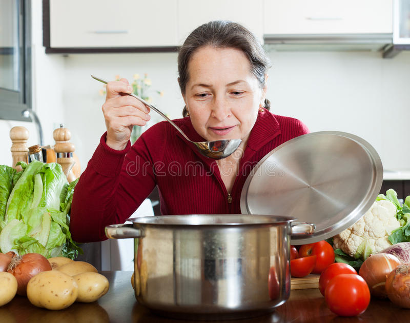 Femme mûre heureuse faisant cuire la soupe prêtée à régime photos stock