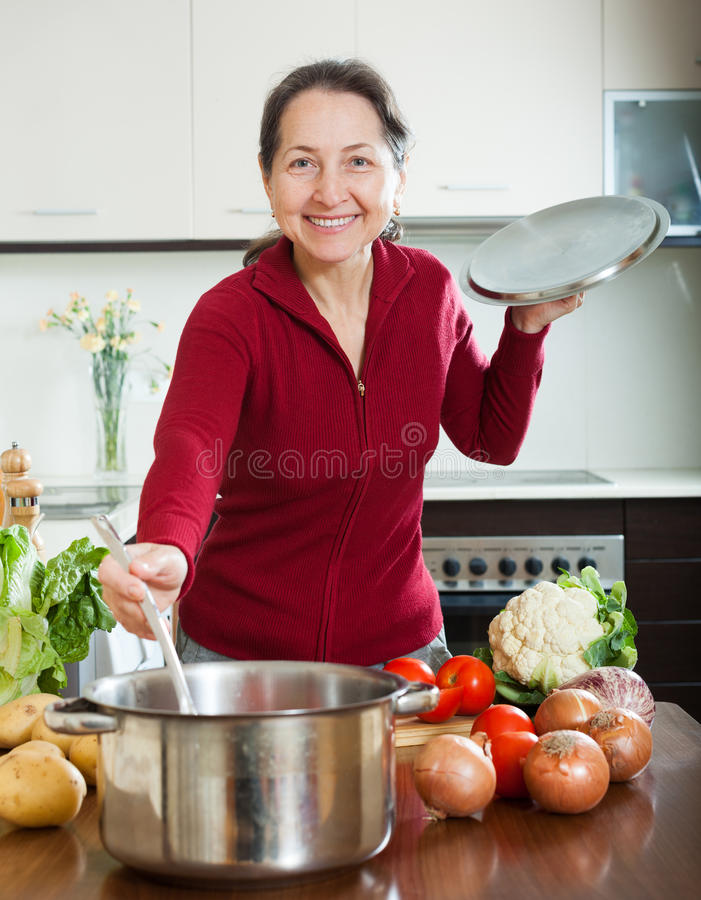 Femme mûre heureuse faisant cuire la soupe prêtée à régime image libre de droits