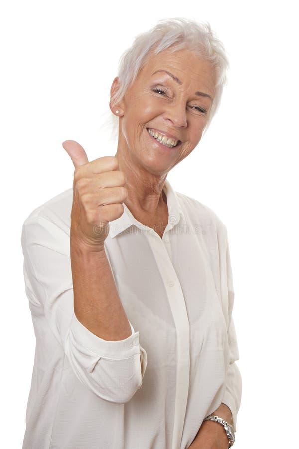 Femme mûre heureuse renonçant à des pouces photos libres de droits