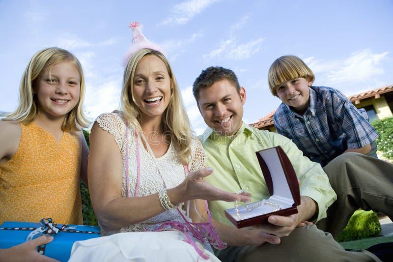 Femme mûre heureuse s'asseyant avec la famille photo stock