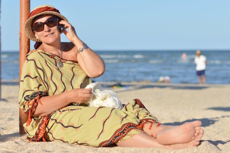 Femme mûre heureuse s'asseyant sur la plage et parlant au téléphone portable image libre de droits