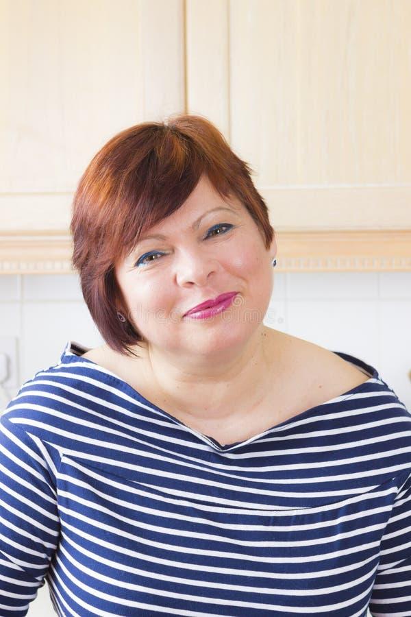 Femme mûre heureuse souriant dans la cuisine photos stock