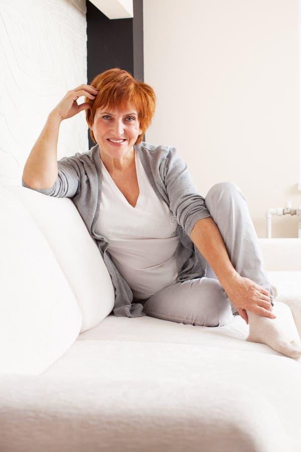 Femme mûre heureuse sur le sofa images libres de droits