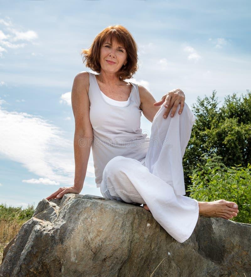 Femme mûre magnifique de yoga détendant dehors photographie stock