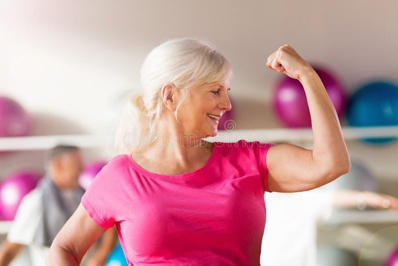 Femme mûre montrant son biceps photographie stock libre de droits