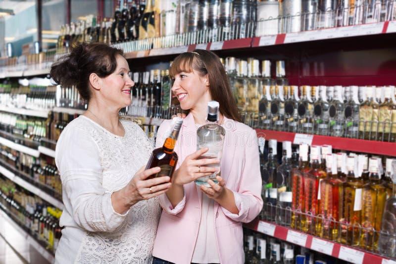 Femme mûre ordinaire et sa fille achetant l'alcool fort images stock