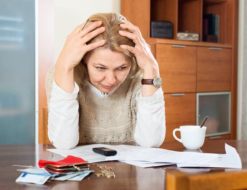 Femme mûre pensant au budget de famille photographie stock libre de droits
