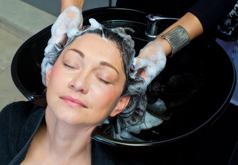 Femme mûre se lavant les cheveux photo stock