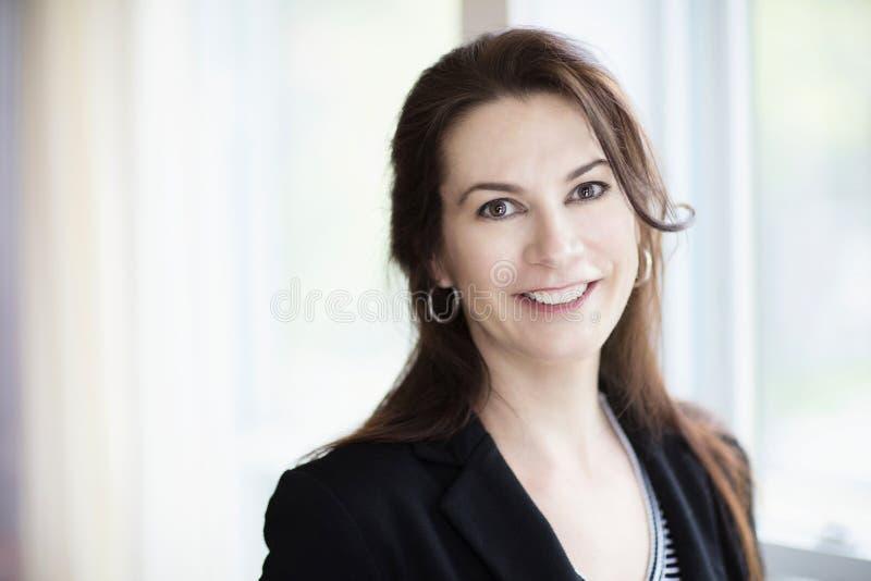 Femme mûre souriant à l'appareil-photo inside photo stock
