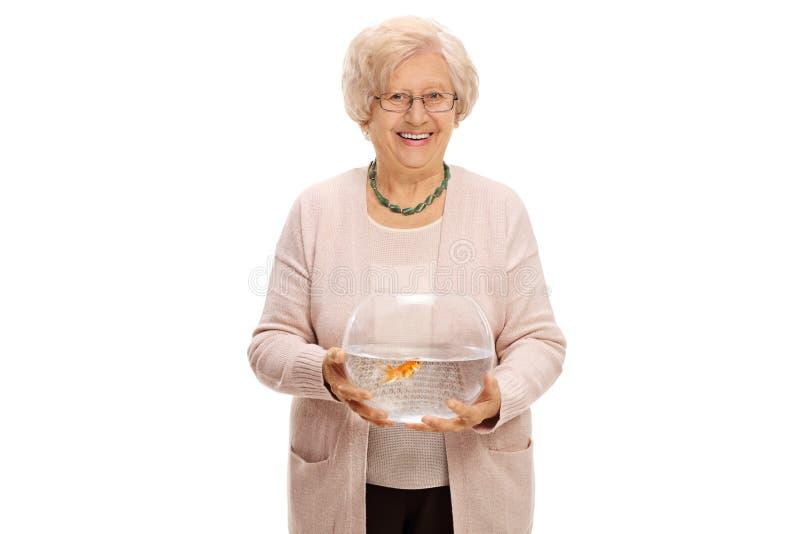Femme mûre tenant une cuvette avec un poisson rouge images stock