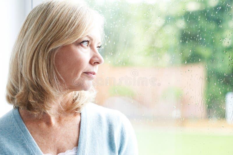 Femme mûre triste souffrant de l'agoraphobie regardant hors de Windo photo stock