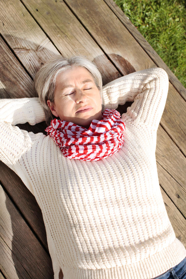 Femme mûrie détendant sur une terrasse images stock