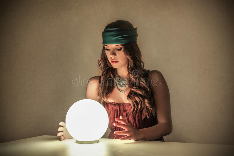 Femme magique regardant une boule de cristal images libres de droits