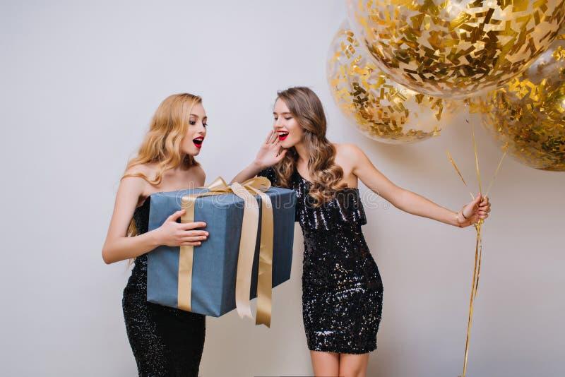 Femme magnifique avec la coiffure élégante tenant le grand cadeau avec l'expression étonnée de visage Photo d'intérieur de deux j image libre de droits