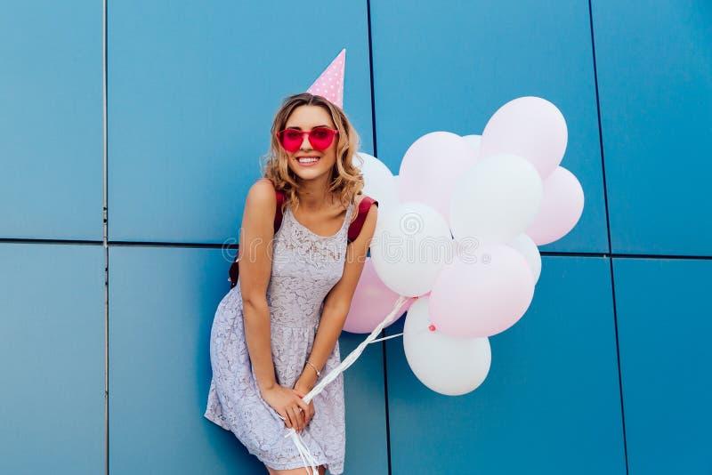 Femme magnifique dans la position de chapeau de partie avec des ballons près du mur urbain image stock