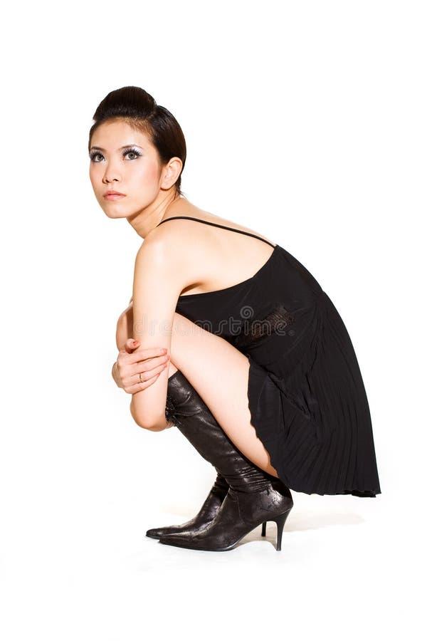 Femme magnifique dans la robe noire s'accroupissant photographie stock