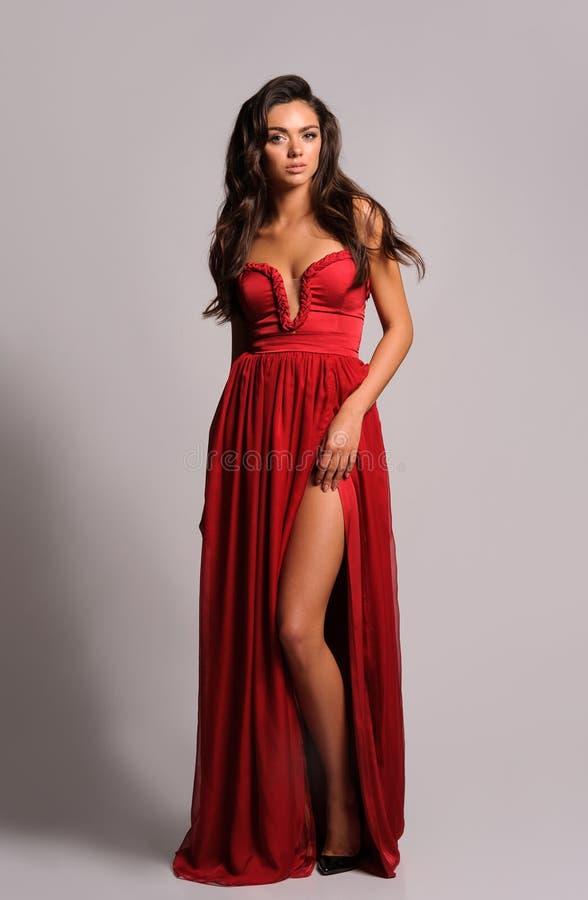 Femme magnifique dans la robe rouge Image de studio, fond gris photo stock