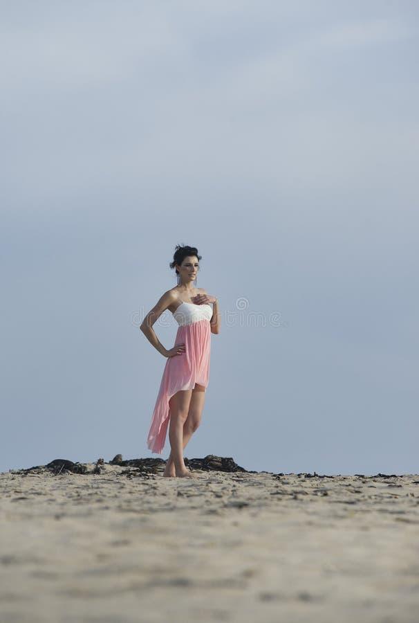 Femme magnifique de brune dans la robe marchant dans le sable de désert photo stock