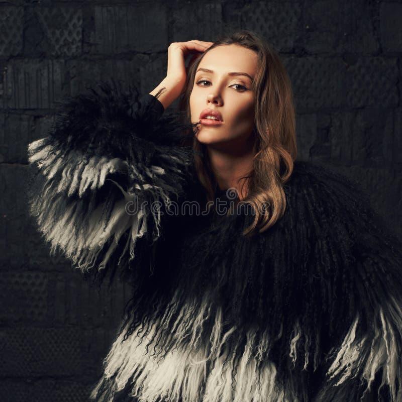 Femme magnifique de brune posant dans le manteau de fourrure de faux au studio photo stock