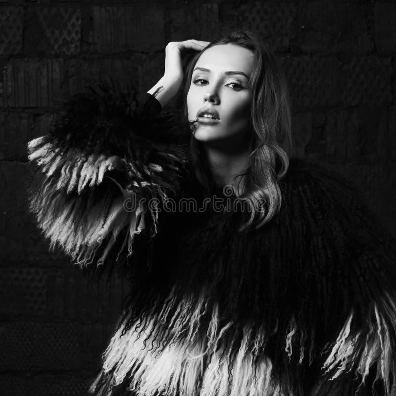 Femme magnifique de brune posant dans le manteau de fourrure de faux au studio images libres de droits